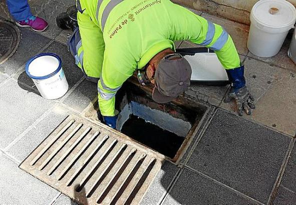 Ein Mitarbeiter der Stadt reinigt einen Abflussschacht, denn dort legen die Tigermücken gern ihre Eier ab