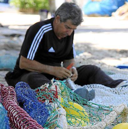 (links). Am Hafen von Palma flicken die Fischer in den Morgenstunden ihre Netze.