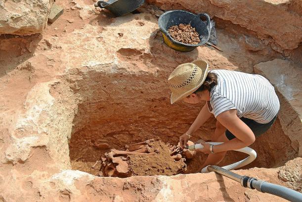 Die Anthropologin Francisca Cardona reinigt Skelett und Fundstätte vorsichtig mit einem Staubsauger.