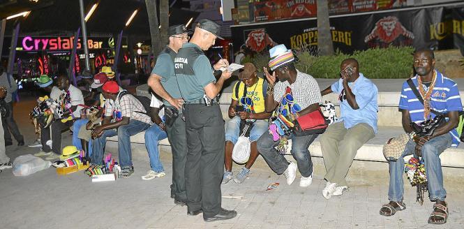 Polizisten kontrollieren Straßenhändler in der Punta Ballena in Magaluf