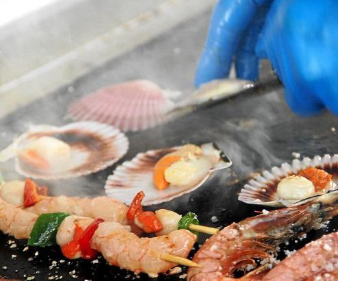 Die Bratküche bietet unter anderem Jakobsmuscheln und Gambas.