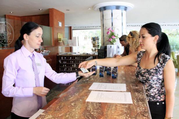 Ein Gast entrichtet an der Hotelrezeption die balearische Übernachtungssteuer.