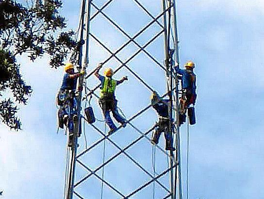 Strompreise am Klettern: Mitarbeiter eines Energiekonzerns auf Menorca überprüfen einen Starkstrommast.