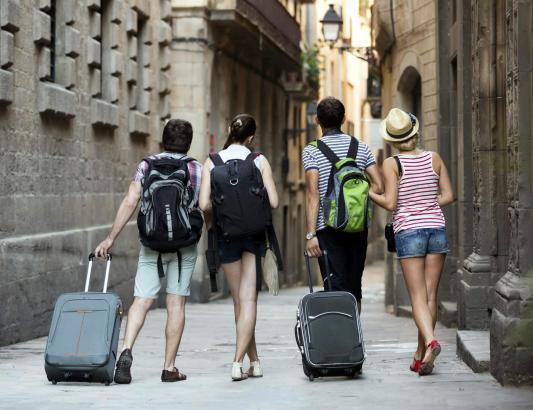 Touristen mit Rollkoffern in der Altstadt.