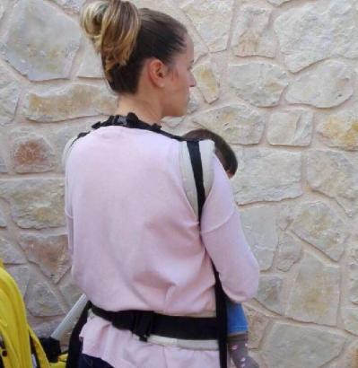 Die Polizistin mit ihrem Kind in einer Tragehilfe