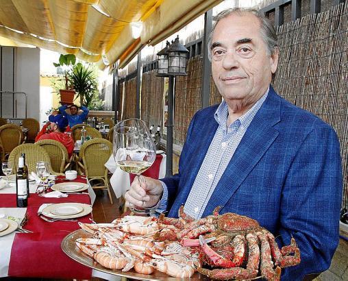 Ex-Hotelier und Unternehmer Antonio Seijas posiert mit Wein und Meeresfrüchten.