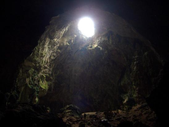 Durch eine Öffnung in der Höhlendecke fällt Licht in die Grotte ein. Zum Größenvergleich: Am unteren Bildrand ist ein Mensch zu