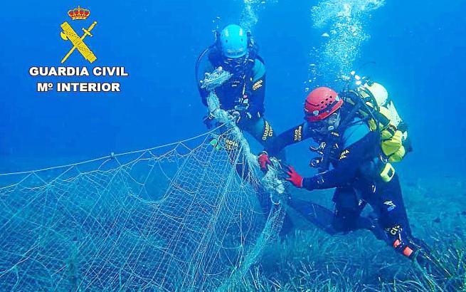 Polizeitaucher inspizieren das Fischernetz