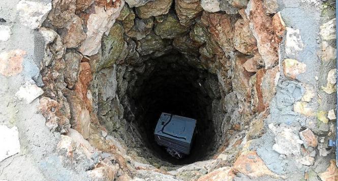 Die Waschmaschine steckt im Brunnenschacht fest.