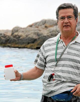 Einer der Kontrolleure des balearischen Gesundheitsministeriums mit Meerwasserprobe am Strand von Illetas.