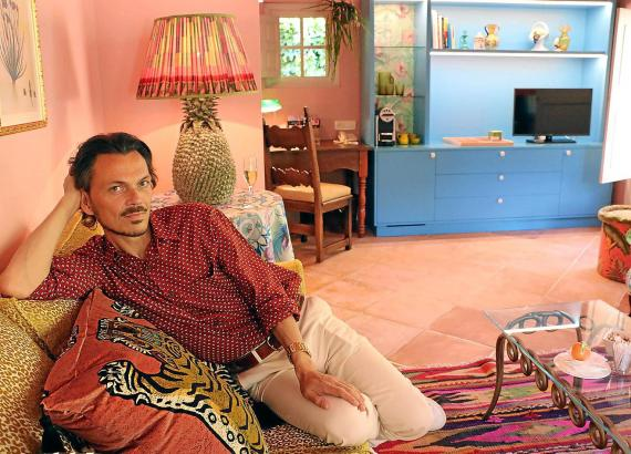 """Der Modeschöpfer hat es sich auf der Couch in der Designersuite des Hotels """"La Residencia"""" gemütlich gemacht."""