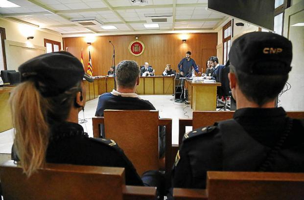 Der Angeklagte während der Gerichtsverhandlung in Begleitung zweier Polizisten.