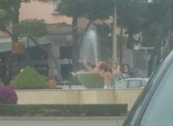 Vier junge Männer plantschen in einem öffentlichen Springbrunnen auf einem Verkehrskreisel in Cala Rajada.