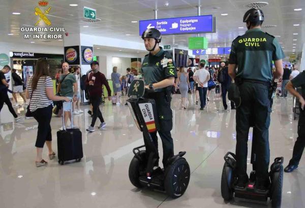 Beamten der Guardia Civil mit den Segways und Schutzhelmen am Flughafen.
