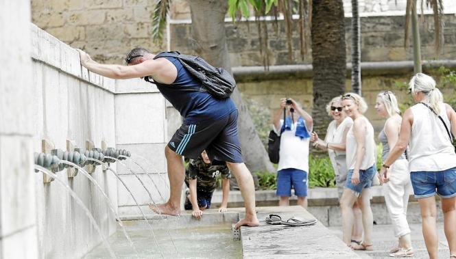 Touristen kühlen sich ihre Füße in einem Brunnen in Palma.
