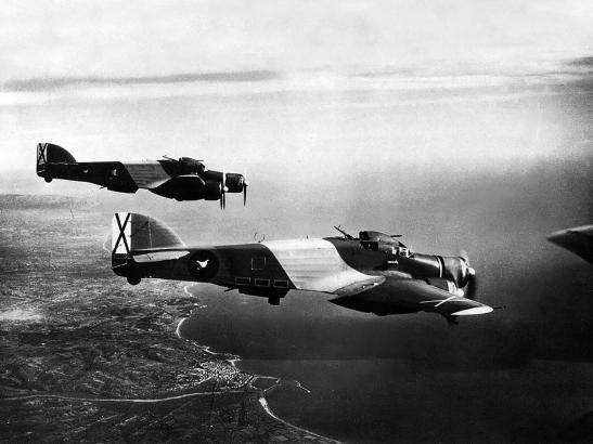 Kampfflugzeuge der Legion Condor überfliegen ein spanisches Küstengebiet.