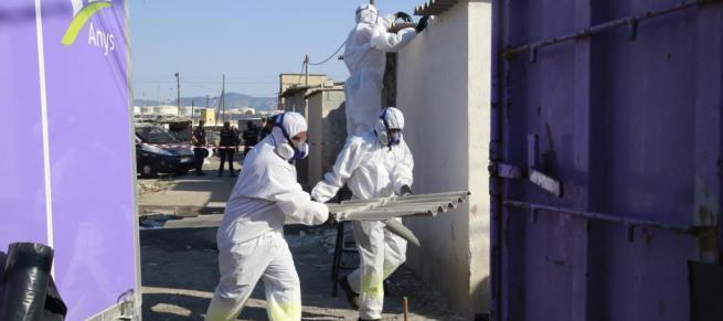 Handwerker in speziellen Schutzanzügen demontieren und entsorgen Asbestbeton-Wellächer der Baracken.