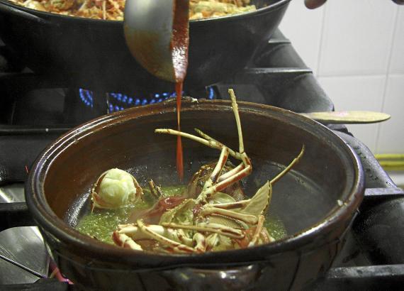 Die köstlichen Meeresfrüchte werden mit einer Sofrito-Mischung und Wasser im Tongefäß erhitzt.