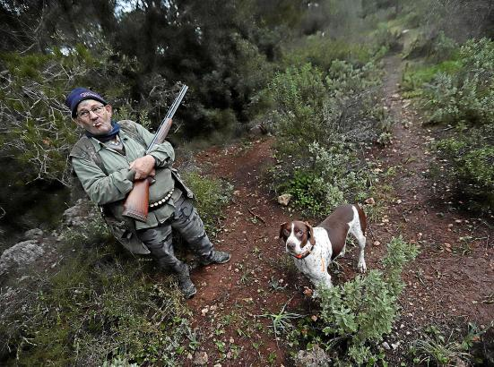 """Jäger Tomeu Salom mit seinem Mischlingshund """"Bobby"""" auf Drosseljagd bei Puntiró nordöstlich von Palma."""