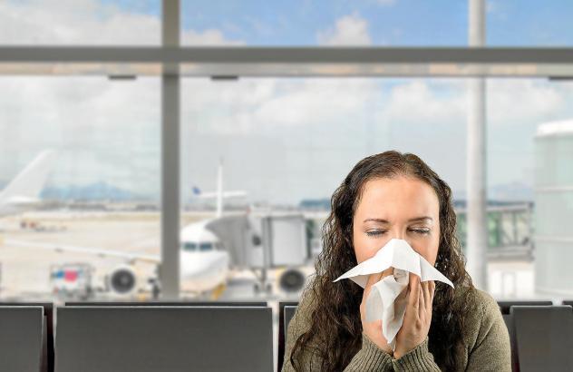 Niesende Frau auf Flughafen.