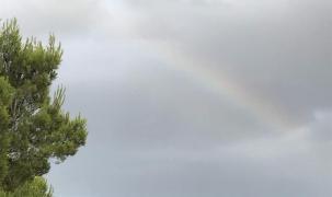 Lichtblick Regenbogen im grauen Himmel