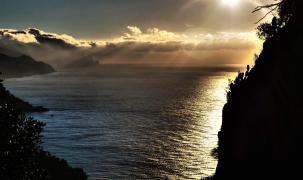 Wolkenverschleierte Sonnenstrahlen treffen die Westküste