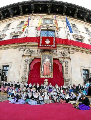 Ratsfrauen und -herren tragen die Standarte auf den Rathausplatz.
