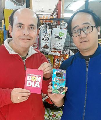 """Journalist Luis Felipe De Lorenzo (l.) und einer der chinesischen Unternehmensberater mit dem Snack """"Tina Berenar""""."""