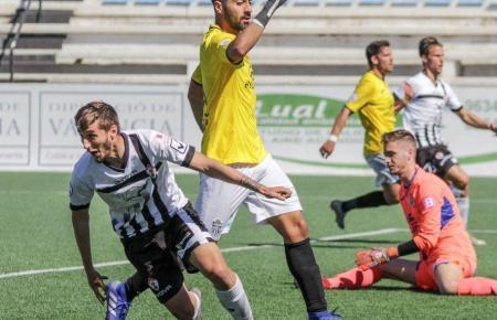 Atlético-Baleares-Kicker Carl Klaus geschlagen am Boden – Ontinyent-Kicker Javi Llor dreht ab und bejubelt seinen Treffer zum 1: