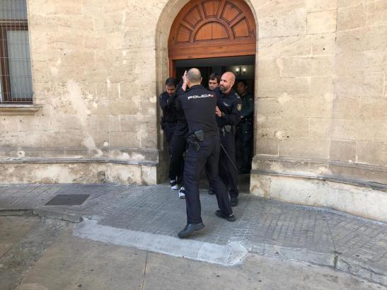 Polizisten führen den Mann aus dem Gerichtsgebäude.