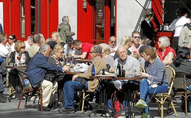 Touristen auf einer Restaurant-Terrasse im Zentrum von Palma.