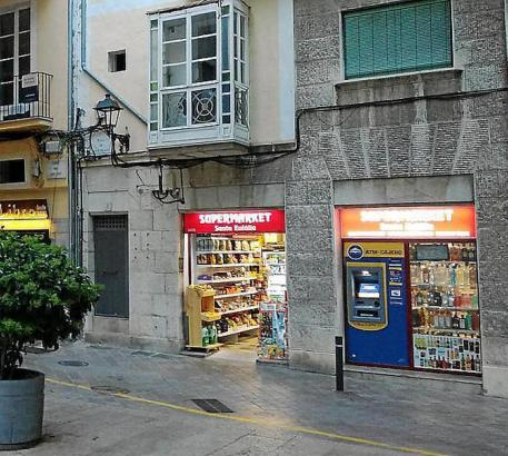 So etwas kritisiert Arca: Leuchtreklame und ein Geldautomat im Schaufenster eines kleinen Ladens.