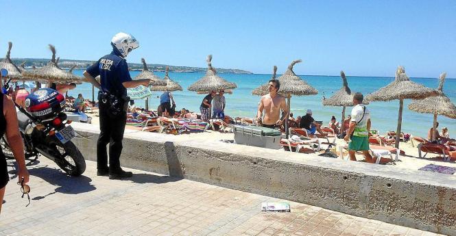 Ein Polizist weist an der Playa de Palma einen Touristen zurecht.