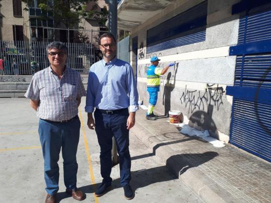 Bürgermeister Hila (r.) vor einer mit Schmiereien verunstalteten Wand.