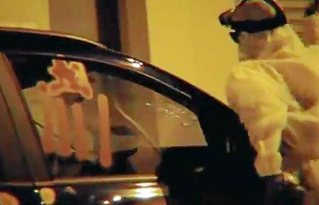 Der Unbekannte schlägt auf ein Auto ein.