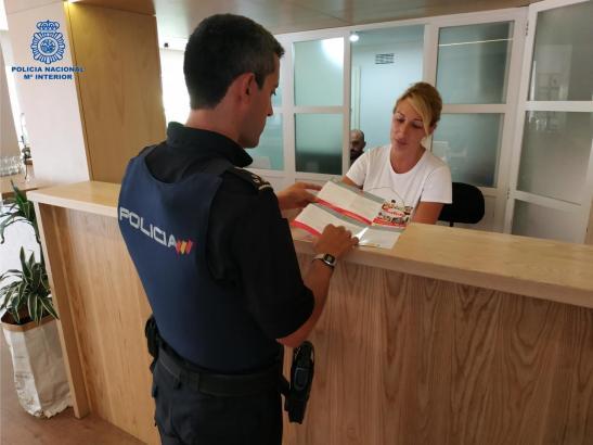 Ein Polizist zeigt der Mitarbeiterin einer Hotelrezeption die Infobroschüre.