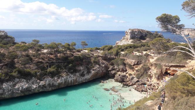 Jetzt im Sommer wird die Bucht Caló des Moro reichlich besucht von Menschen, die Abkühlung im Meer suchen.