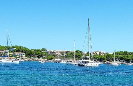 Boote ankern im Naturhafen von Portocolom vor dem Strand von S'Arenal.