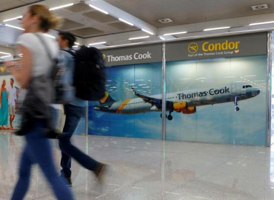 Touristen vor Thoma-Cook-Werbung im Flughafen Palma.