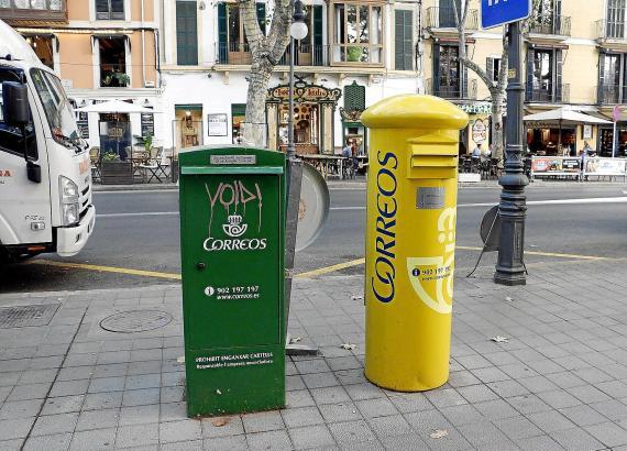 Ein grüner und ein gelber Briefkasten.