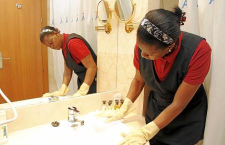 Ein Zimmermädchen reinigt das Badezimmer eines Hotels.