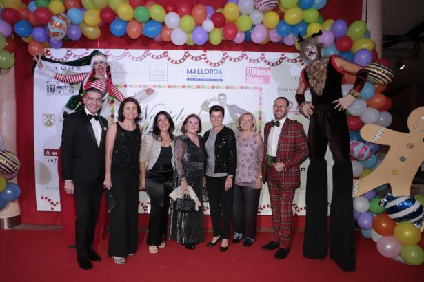 "Esteban Mercer, Paula Serra, Carmen Zaforteza, Carmen Dameto, Carmen Serra, Maria Lluc Dameto und Joan Conejo (von links nach rechts) bei ""Navidad entre amigos"" mit zwei lustigen Stelzen-Gestalten."