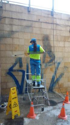 Mitarbeiterin der Stadt entfernt Graffiti.