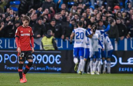 Die Spieler von Real Saragossa jubeln im Hintergrund, Real Mallorcas Aleix Febas schiebt Frust.