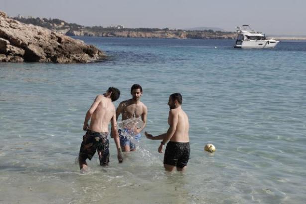Drei junge Spanier haben bei einer Wassertemperatur von 15 Grad am Strand von Illetes viel Spaß.