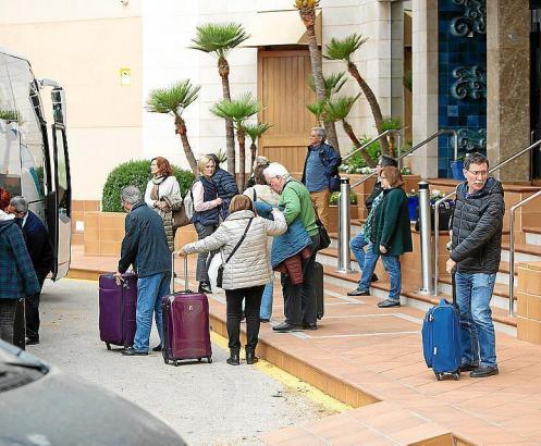 Touristen neben einem Hotel auf Mallorca besteigen einen Bus.