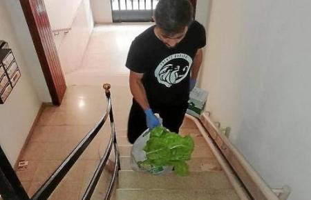 Ein Freiwilliger trägt die Einkäufe nach oben. Handschuhe und Sicherheitsabstand sind ein Muss. Mundschutzmasken waren für die Freiwilligen nicht mehr zu bekommen.