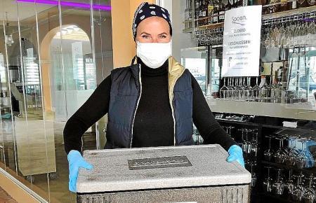"""Heidi Lübke vom Restaurant """"Spoon"""" in Puerto Portals auf dem Weg zum nächsten Lieferservice-Kunden. Das Personal schützt sich durch Mundschutz und Handschuhe."""