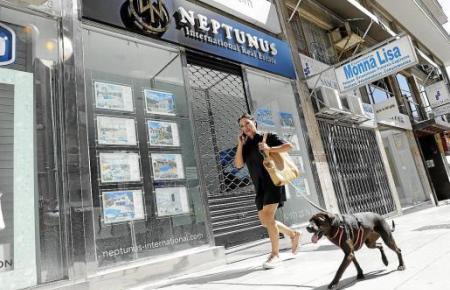 Eine Frau mit Handy am Ohr führt einen Hund in Palma Gassi. Rückkehr zur Normalität?