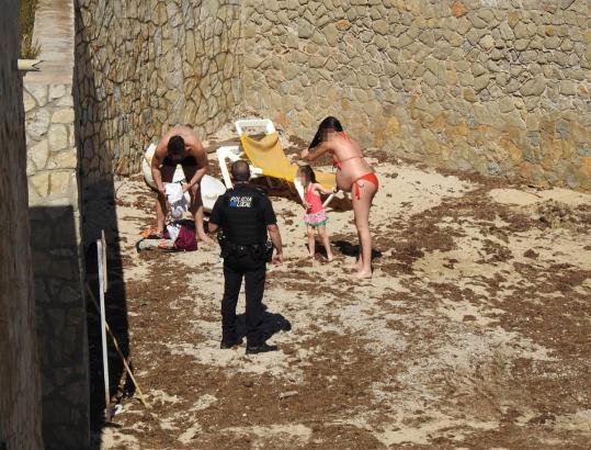 Ein Polizist weist eine Familie darauf hin, dass sie zu verschwinden hat.